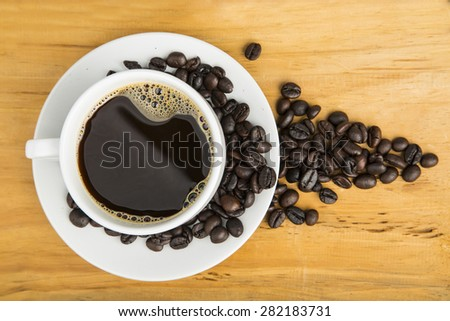 Coffee cup with beans on the wood board. - stock photo