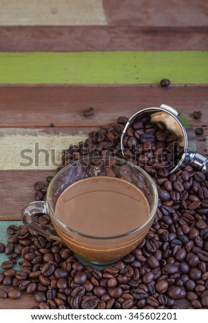 Coffee cup with beans on wooden background - stock photo