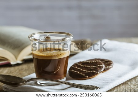 Coffee cup with book on a wooden background with a brick texture - stock photo