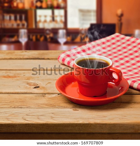 Coffee cup with checked tablecloth on wooden table - stock photo