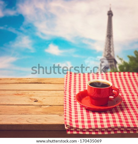 Coffee cup with checked tablecloth on wooden table over Eiffel tower in Paris, France - stock photo