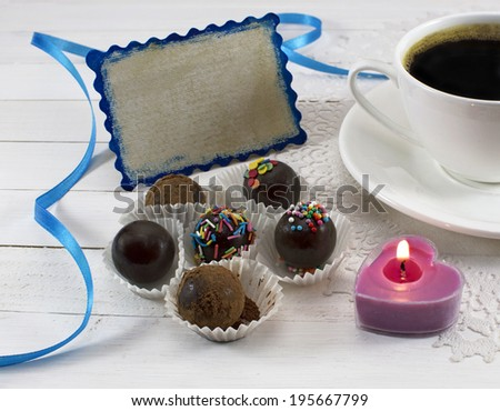 Coffee cup with chocolate candies, burning candle and greeting card - stock photo