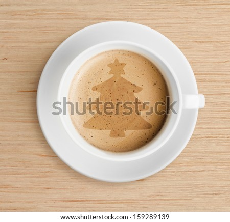 coffee cup with christmas tree shape on foam - stock photo