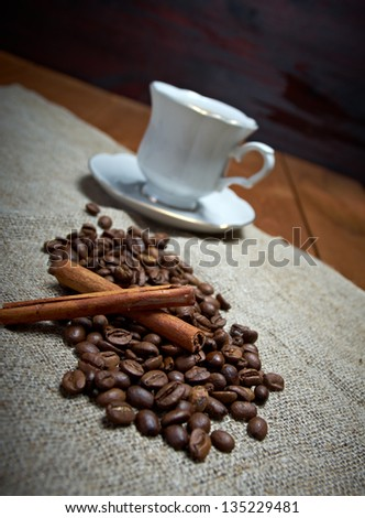 Coffee cup with cinnamon and coffee beans background