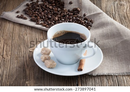 Coffee cup with cinnamon, cane sugar on wooden background - stock photo