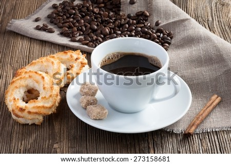 Coffee cup with coconut cookies, cinnamon and cane sugar on wooden background - stock photo