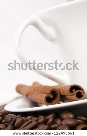 Coffee cup with coffee beans and cinnamon.