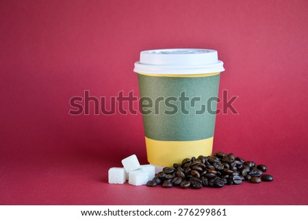 Coffee cup with coffee beans and sugar cubes on red background - stock photo