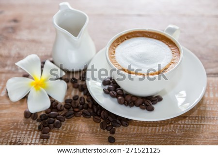 Coffee cup with coffee beans and white flowers. - stock photo