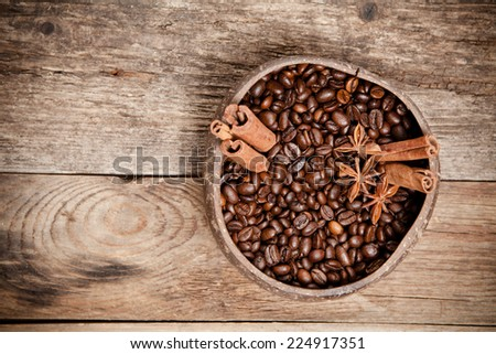 Coffee cup with coffee beans, cinnamon, star anise on old wooden table. Top view. - stock photo