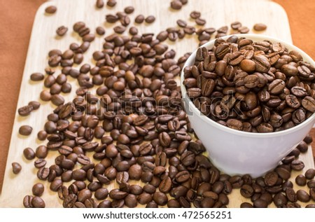 Coffee Cup with coffee beans on wood of coffee beans background