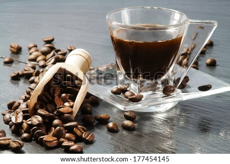 coffee cup with coffee beans over ardesia - stock photo