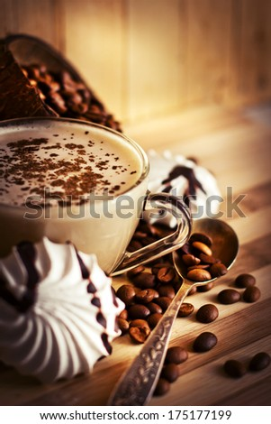 Coffee cup  with coffee beans over wooden background - stock photo