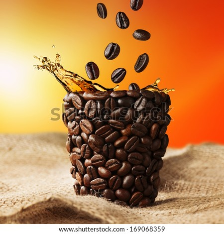 coffee cup with coffee splash and beans falling