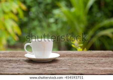 Coffee cup with coffee stains edge on wooden in the backyard Natural background