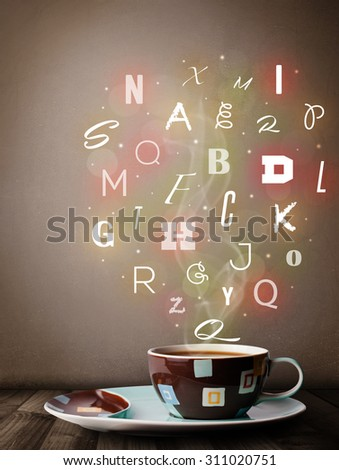 Coffee cup with colorful letters, close up - stock photo