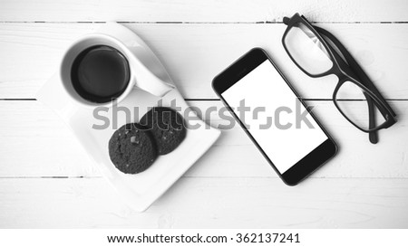 coffee cup with cookie,phone and eyeglasses on white wood table black and white color