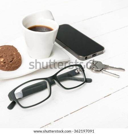 coffee cup with cookie,phone,eyeglasses and key on white wood background