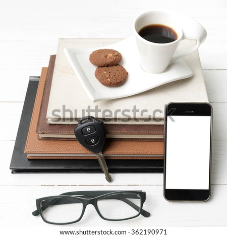 coffee cup with cookie,phone,stack of book and car key on white wood table