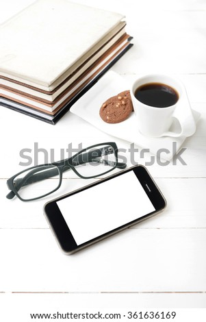 coffee cup with cookie,phone,stack of book and eyeglasses on white wood table