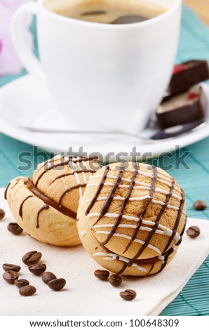 Coffee cup with cookie sandwich on the table