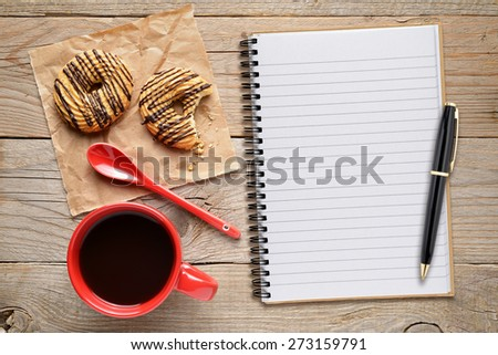Coffee cup with cookies and notepad with pen on wooden table - stock photo