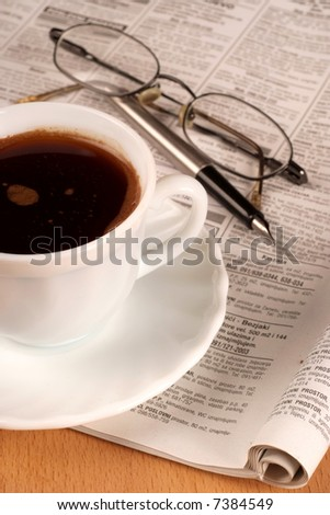 Coffee cup with glasses and newspaper - stock photo