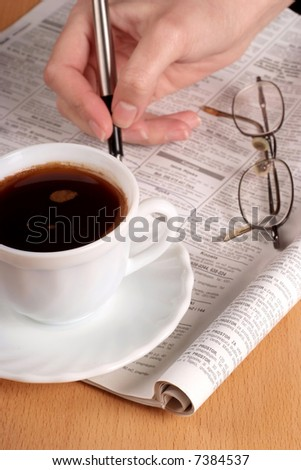 Coffee cup with glasses and newspaper. Focus on cup. - stock photo