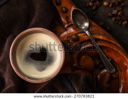 coffee cup with heart shape made of foam on old colonial wooden table, top view, close up