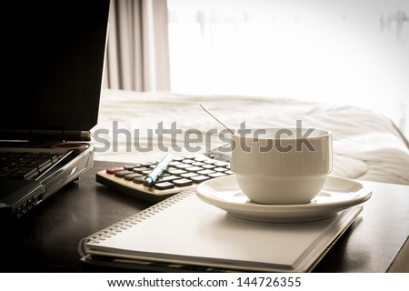 coffee cup with laptop and notebook and Calculator onthe table in bed room - stock photo