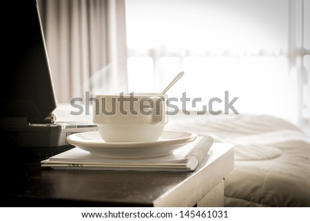 coffee cup with laptop and notebook on the table in bed room - stock photo