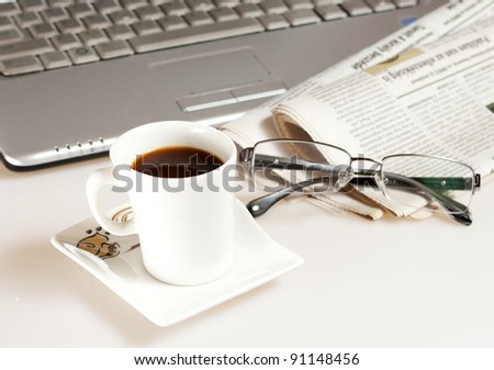 Coffee cup with laptop, glasses and newspaper - stock photo