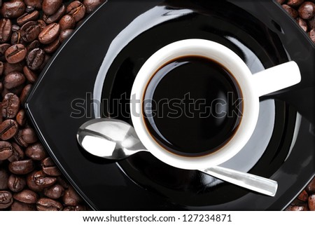 Coffee cup with metal spoon and beans, top view - stock photo