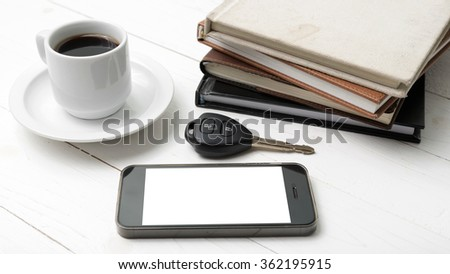 coffee cup with phone,car key and stack of book on white wood table