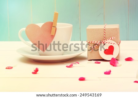 Coffee cup with pink heart tag and a small gift box - stock photo