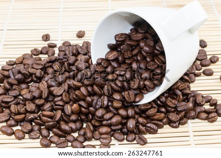 Coffee Cup with roasted coffee beans on heap of bamboo brown straw mat for background
