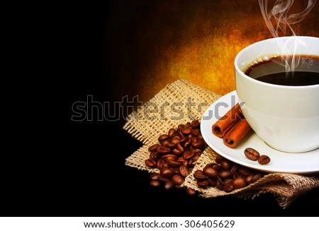 Coffee cup with saucer and coffee beans on burlap over dark background