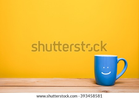 coffee cup with smile on yellow background - stock photo