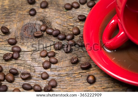 Coffee cup with spilled coffee and coffee beans on table - stock photo