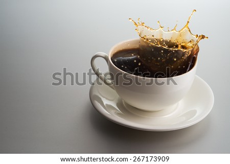 Coffee cup with splashes on white background - stock photo