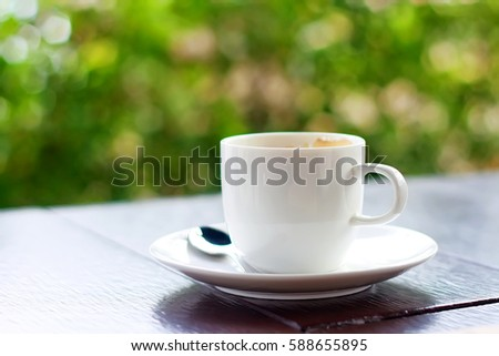 coffee cup with spoon and saucer on wood table on natural background