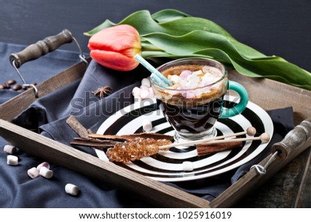 Coffee cup with sugar and spices on a wooden board.
