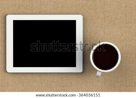 Coffee cup with tablet on brown fabric table
