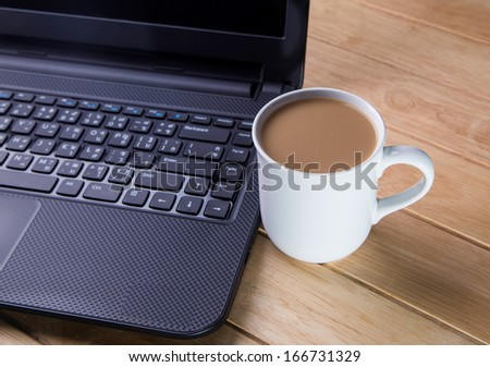 Coffee cup with the computer on a wooden table.