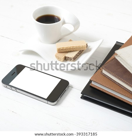 coffee cup with wafer,phone,stack of book on white wood background