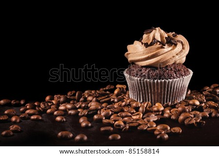 Coffee cupcake & coffee beans on black background - stock photo