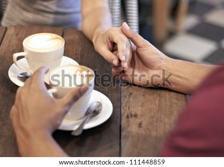 Coffee cups and holding hands at the wooden table - stock photo