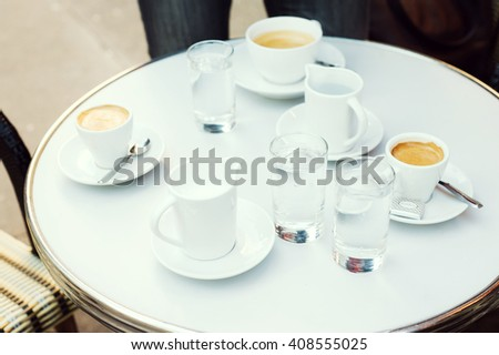Coffee cups, milk and water glass in a Parisian outdoors cafe in Paris, France