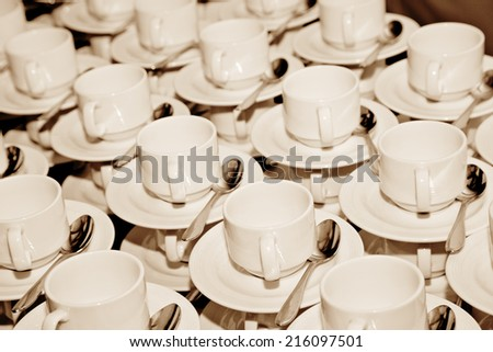 coffee cups, plate and spoon composition in a restaurant. Sepia - stock photo