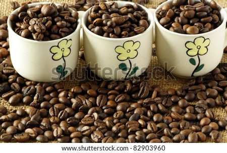 coffee cups with coffee beans on the background - stock photo